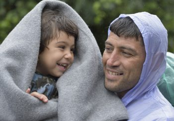 Refugees on their way to western Europe, a man from Iran holds his son as they approach the border into Croatia near the Serbian village of Berkasovo. The ACT Alliance has provided critical support for refugee and migrant families here and in other places along their journey. Photo: Paul Jeffrey/ACT